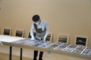 会場内の長テーブルに、畠山直哉さんが震災以降に撮り続けた写真のコンタクトシート556枚を1枚ずつ並べていきます。貴重な写真作品の展示であることから、取り扱いには細心の注意を払って作業をしていきます。